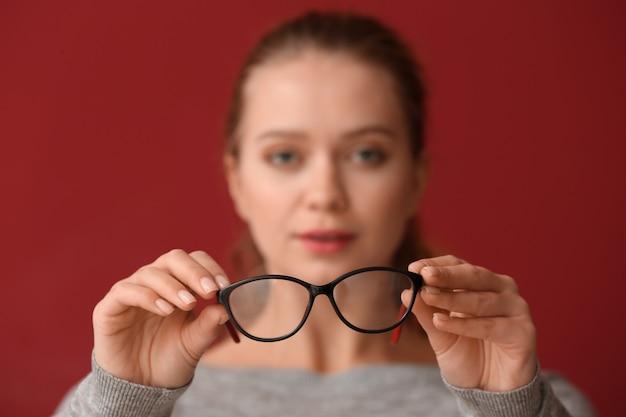 Mujer joven, con, mala vista, tenencia, anteojos