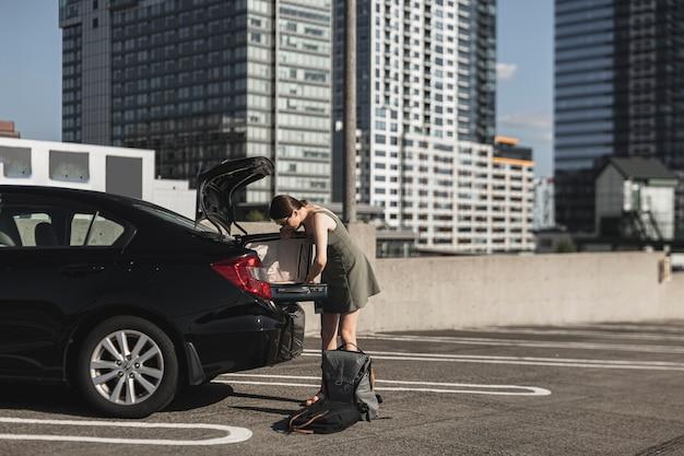 Mujer joven con una maleta abierta en la cajuela del automóvil