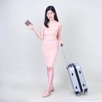 Mujer joven con maleta en blanco