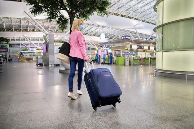 Mujer joven con una maleta caminando en el aeropuerto