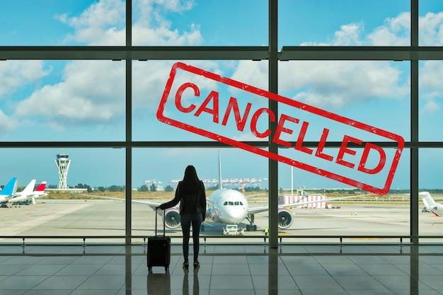 Mujer joven con maleta en la sala de salidas del aeropuerto.