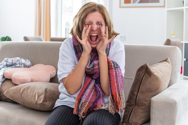 Mujer joven malsana con bufanda caliente alrededor del cuello que se siente terrible que sufre de virus gritando de pánico sentado en el sofá en la sala de estar iluminada