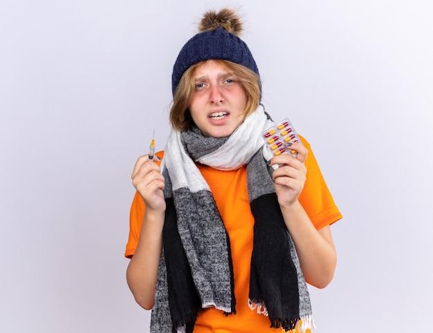 Mujer joven malsana en camiseta naranja con bufanda caliente alrededor del cuello y sombrero sintiendo terrible sufrimiento de gripe con jeringa y píldoras