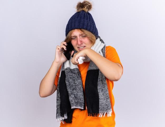 Mujer joven malsana en camiseta naranja con bufanda caliente alrededor del cuello y sombrero sintiéndose terrible hablando por teléfono móvil soplando la nariz estornudando en el tejido