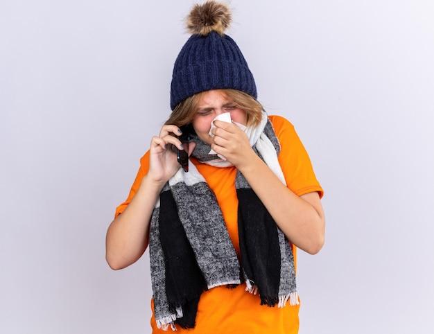 Mujer joven malsana en camiseta naranja con bufanda caliente alrededor del cuello y sombrero sintiéndose terrible hablando por teléfono móvil soplando la nariz que gotea estornudando en un pañuelo de pie sobre una pared blanca