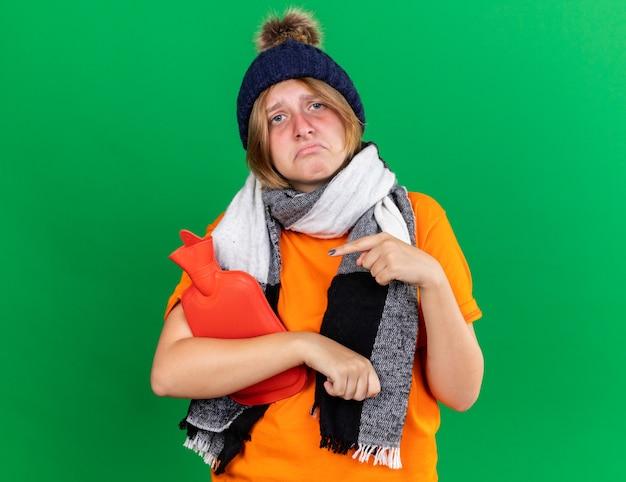 Mujer joven malsana en camiseta naranja con sombrero y bufanda caliente alrededor del cuello sensación terrible sosteniendo una botella de agua caliente que sufre de frío