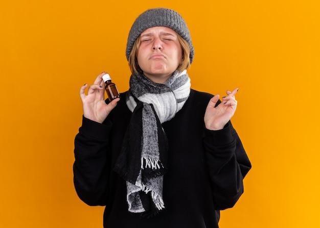 Mujer joven malsana con gorro y bufanda alrededor de su cuello sintiéndose enferma sufriendo de resfriado y gripe sosteniendo un frasco de medicina con los ojos cerrados cruzando los dedos