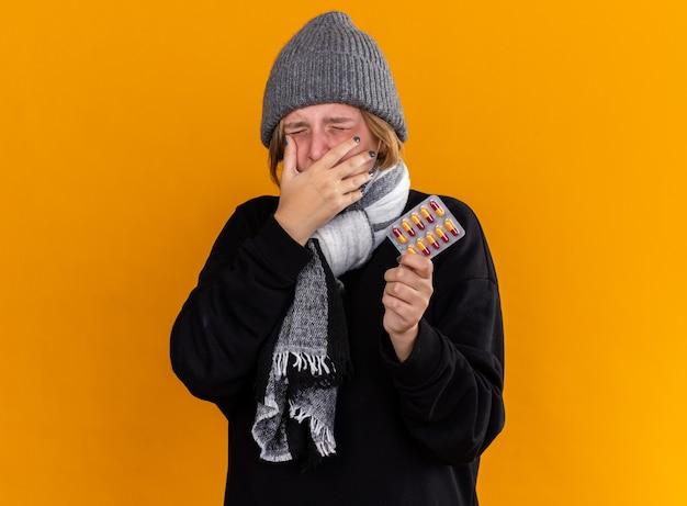 Mujer joven malsana con gorro y bufanda alrededor de su cuello sintiéndose terrible sufrimiento de resfriado y gripe sosteniendo pastillas cubriendo la boca con la mano estornudando de pie sobre la pared naranja