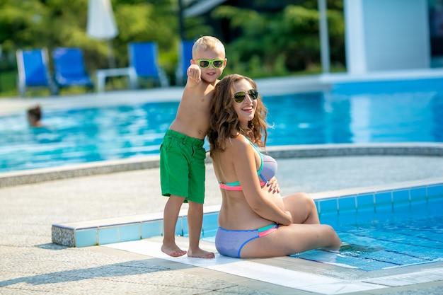 Mujer joven mamá con bebé juntos de vacaciones en la piscina.