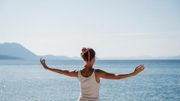 Mujer joven mañana meditación junto al mar