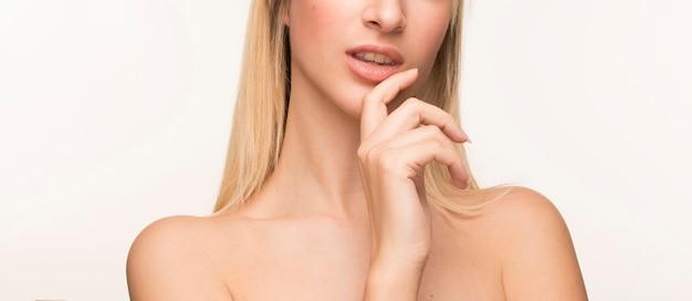 Mujer joven con la mano en la barbilla