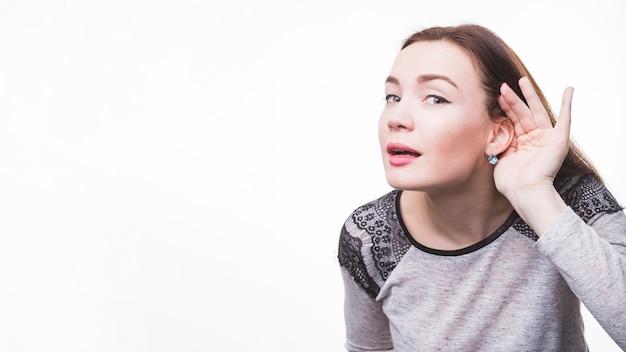 Mujer joven con la mano detrás de la oreja escuchando de cerca