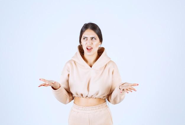 Mujer joven con las manos abiertas para presentar y hablar de algo