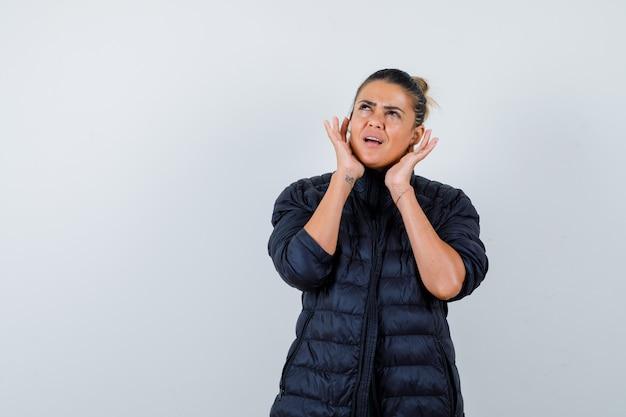 Mujer joven con las manos cerca de las orejas, mirando hacia arriba con chaqueta acolchada y mirando confundido. vista frontal.