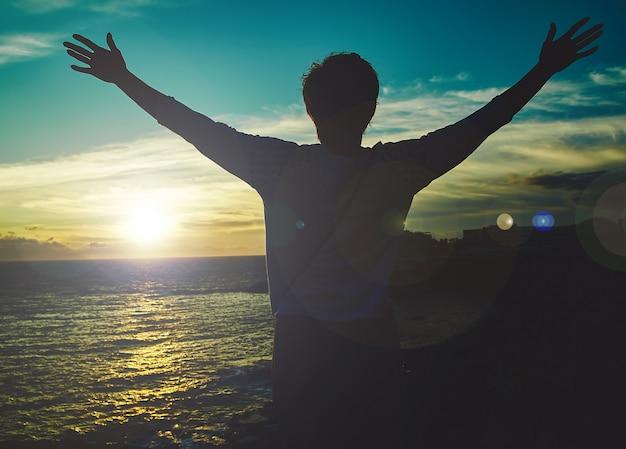 Mujer joven con las manos levantadas saludo sol