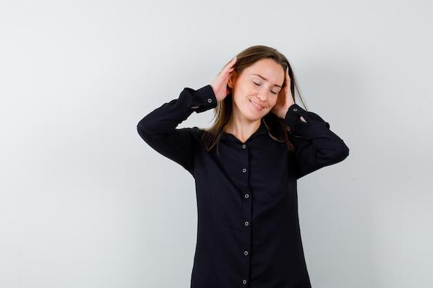 Mujer joven, manos de valor en cartera, detrás de la cabeza