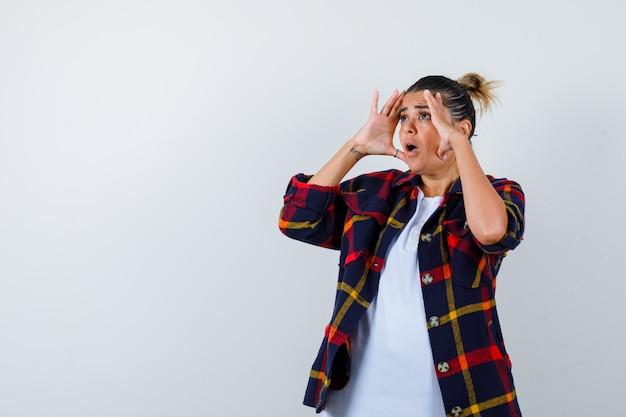 Mujer joven con las manos para ver con claridad, de pie de lado con camisa a cuadros y mirando consternado.