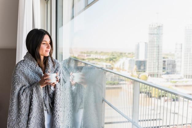 Mujer joven con una manta sobre su hombro sosteniendo una taza de café en la mano mirando lejos