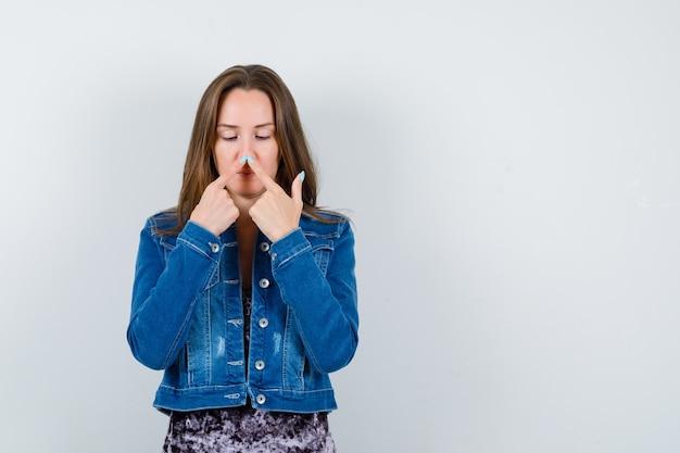 Mujer joven manteniendo los dedos en la nariz en chaqueta de mezclilla, vestido y mirando divertido, vista frontal. Foto gratis