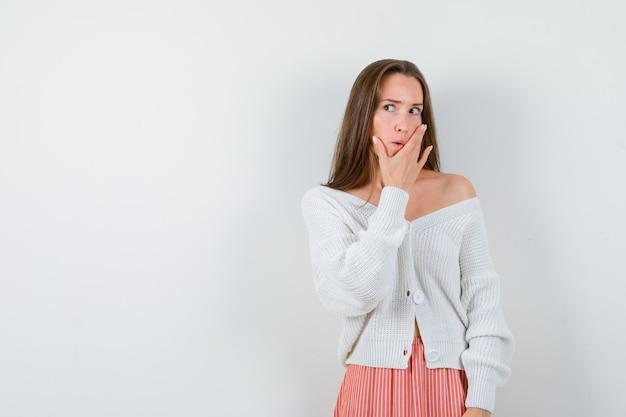 Mujer joven manteniendo la mano en la barbilla en chaqueta y falda mirando curioso aislado