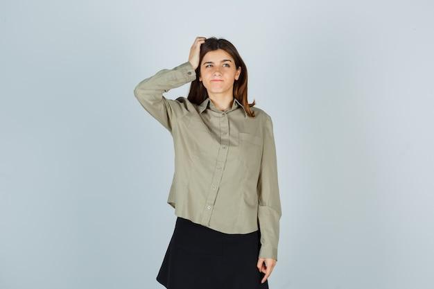 Mujer joven manteniendo la mano en la cabeza, frunciendo los labios en camisa, falda y mirando pensativo