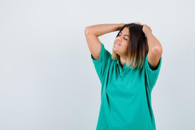 Mujer joven manteniendo las manos en la cabeza en camiseta de polo y mirando relajado. vista frontal.