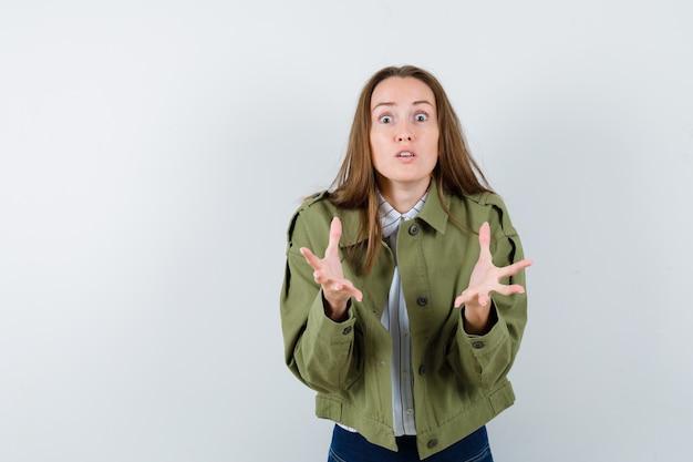 Mujer joven manteniendo las manos en gesto de perplejidad en camisa, vista frontal.
