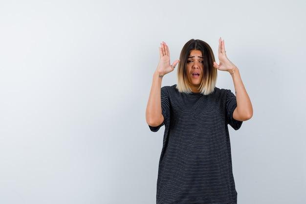Mujer joven manteniendo las manos de manera agresiva en vestido de polo y luciendo estresada. vista frontal.