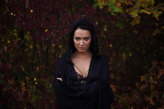 Mujer joven en el manto negro en el bosque de otoño
