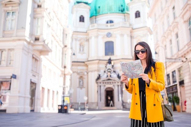Mujer joven con un mapa de la ciudad en la ciudad