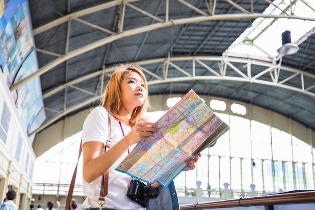 Mujer joven con el mapa en la estación de tren