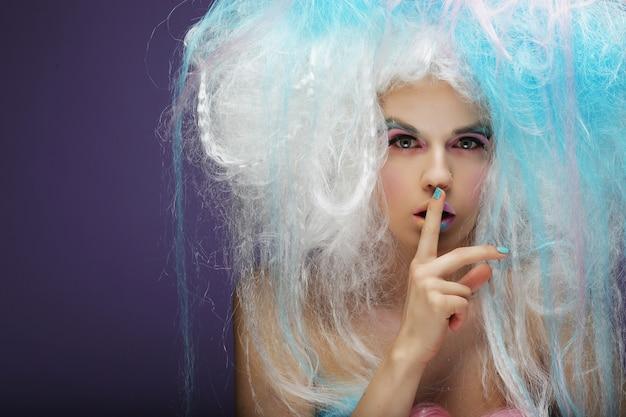 Mujer joven con maquillaje brillante y cabello creativo