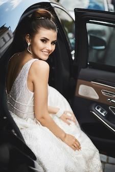 Mujer joven con maquillaje brillante en un moderno vestido plateado con espalda desnuda sentada en el auto de lujo