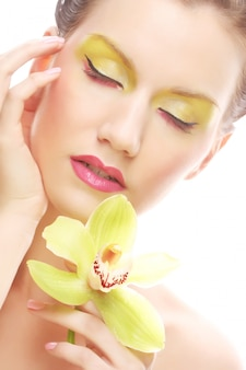 Mujer joven con maquillaje brillante con orquídea