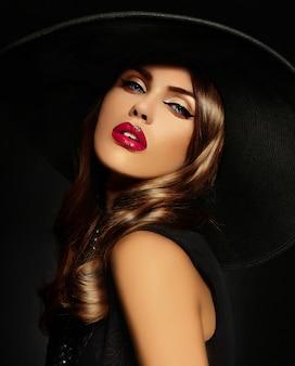 Mujer joven con maquillaje brillante y sombrero negro
