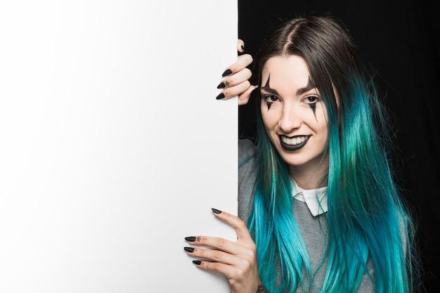 Mujer joven con maquillaje emergente detrás de la pizarra