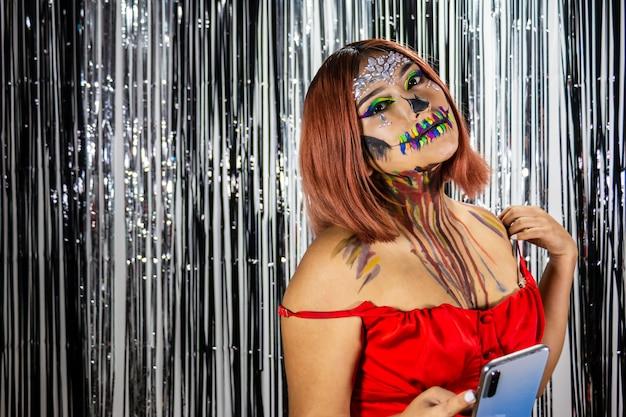 Mujer joven con maquillaje para fiesta de halloween fondo blanco y negro brillante teléfono celular en la mano
