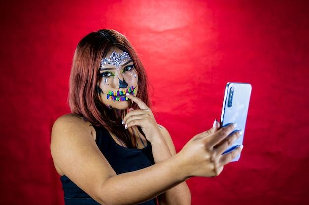 Mujer joven con maquillaje para fiesta de halloween toma un selfie desde su teléfono celular