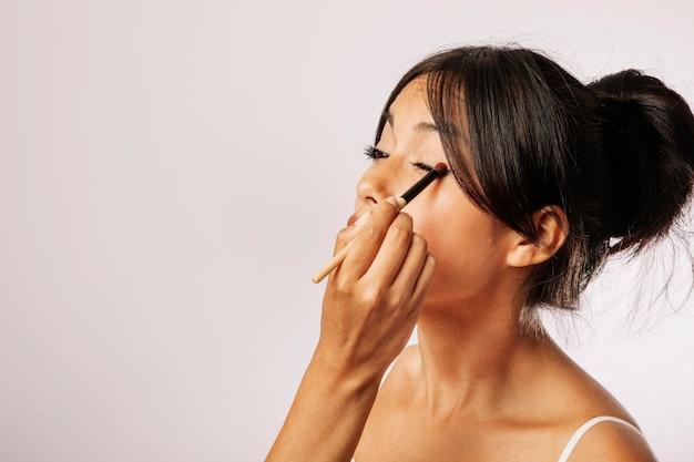 Mujer joven con maquillaje de ojos