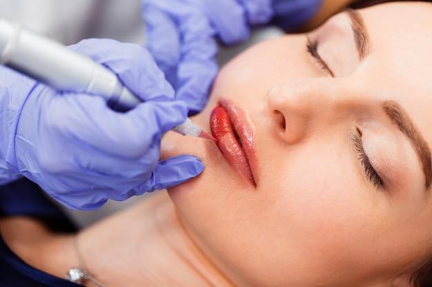 Mujer joven con maquillaje permanente en los labios en el salón de belleza.