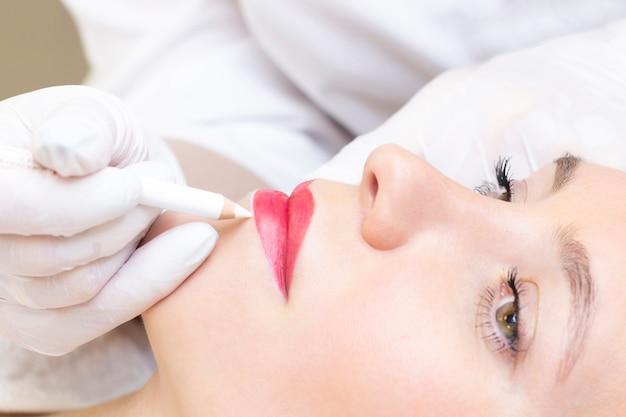 Mujer joven con maquillaje permanente en sus labios en el salón de belleza. maquillaje permanente. dibujar un contorno con un lápiz labial blanco