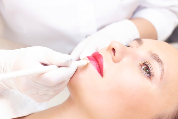 Mujer joven con maquillaje permanente en sus labios en el salón de esteticistas. maquillaje permanente