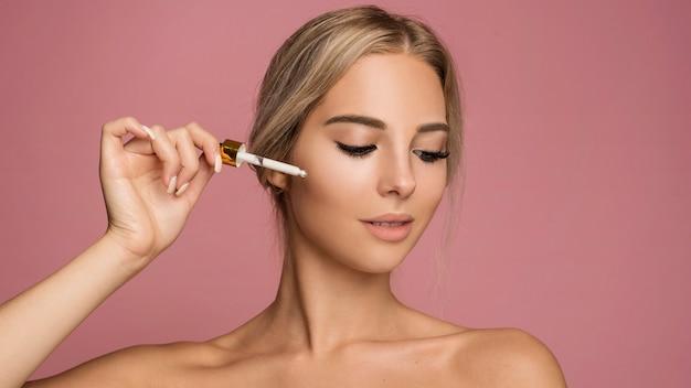 Mujer joven con maquillaje pipeta