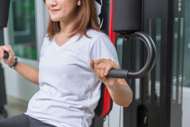 Mujer joven en la máquina de entrenamiento muscular del pecho del gimnasio