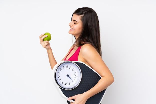 Mujer joven con máquina de pesaje y una manzana