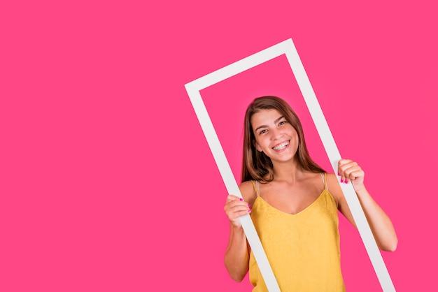 Mujer joven en el marco blanco en fondo rosado