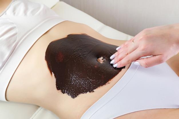 Mujer joven en un masaje de chocolate. envoltura de vientre de chocolate. tratamiento de spa.