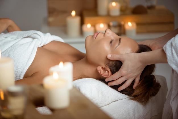 Mujer joven con masaje facial relajante en el salón de spa.