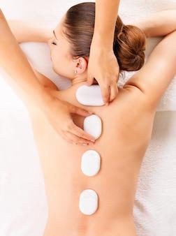 Mujer joven con masaje con piedras calientes en el salón de spa. concepto de tratamiento de belleza.