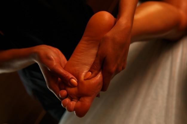 Mujer joven con masaje de pies en salón de belleza